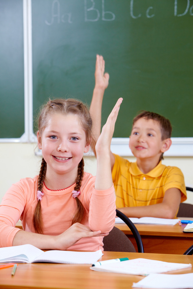 Portrait Of Lovely Girl Raising Hand At Workplace With Schoolboy On Background