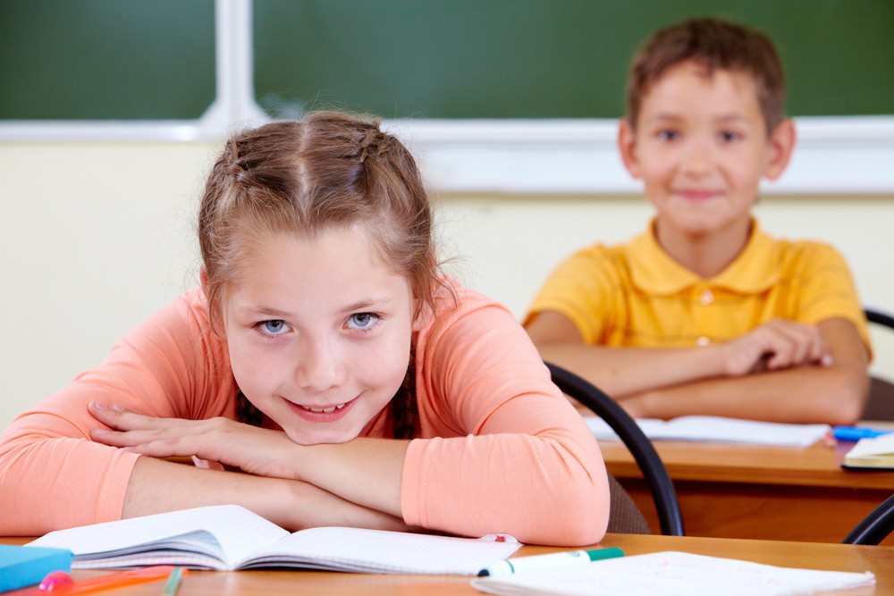 Portrait Of Lovely Girl At Workplace Looking At Camera With Schoolboy On Background