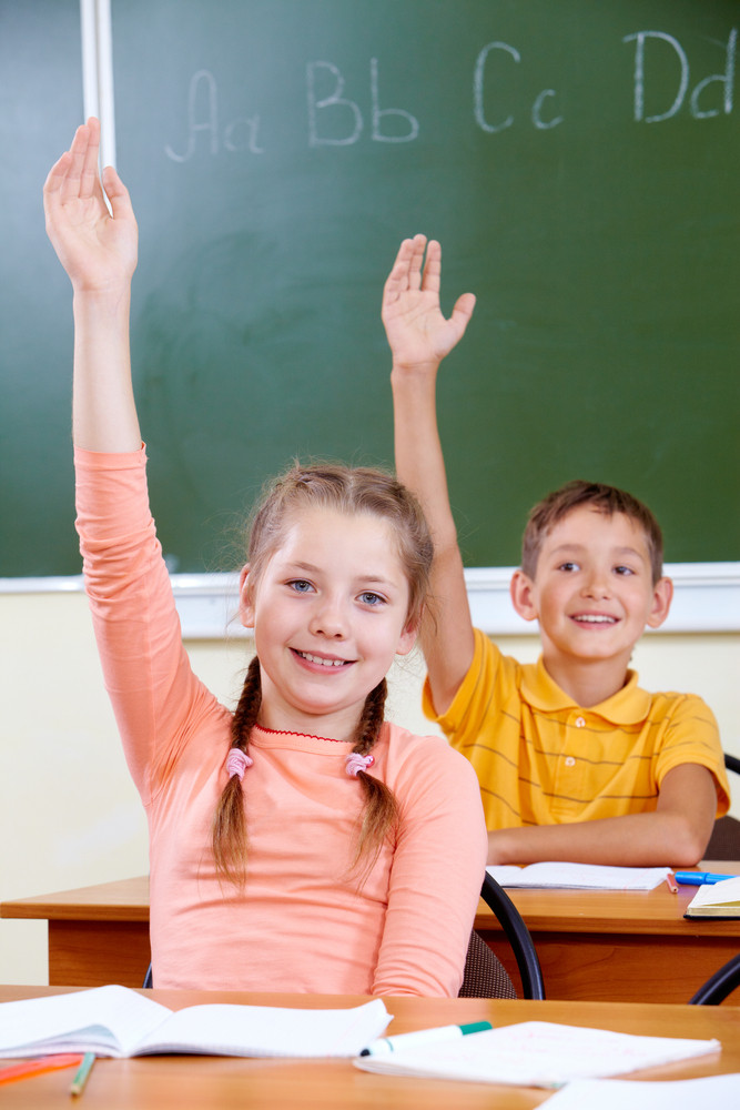 Portrait Of Lovely Girl And Her Classmate On Background Raising Hands At Lesson