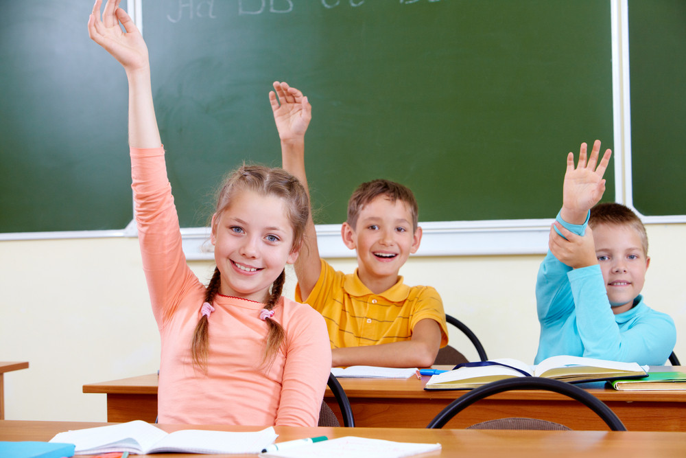 Portrait Of Cute Schoolgirl And Her Classmates On Background Raising Hands At Lesson