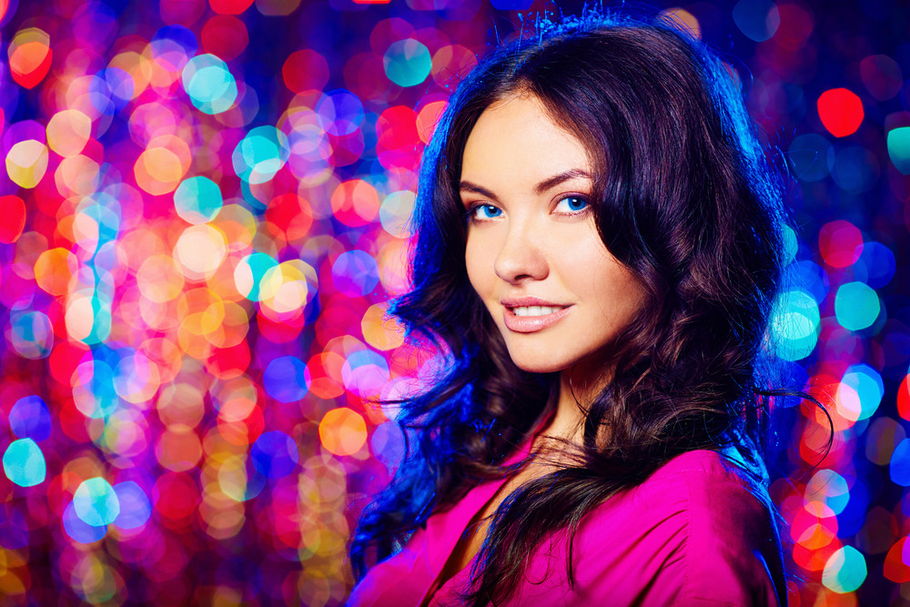 Charming Woman Looking At Camera Over Sparkling Background