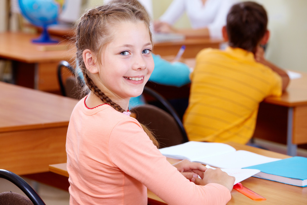 Portrait Of Lovely Girl At Workplace With Schoolboys On Background