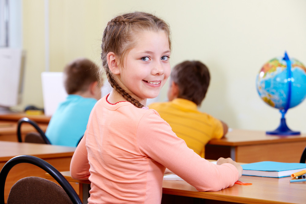 Portrait Of Lovely Girl Looking At Camera At Workplace With Schoolboys On Background