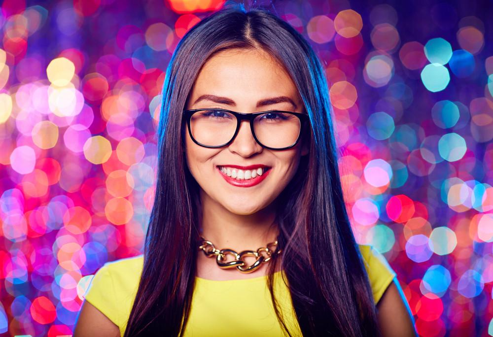 Asian Female In Eyeglasses Looking At Camera At Party