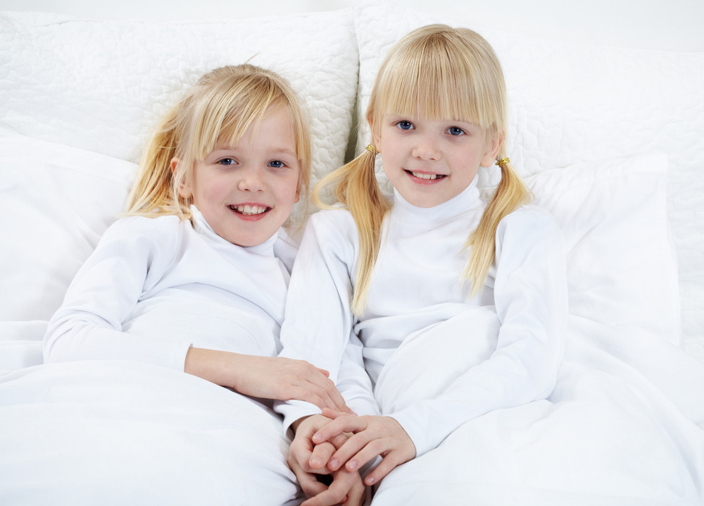 Portrait Of Cute Twins Lying In The Bed