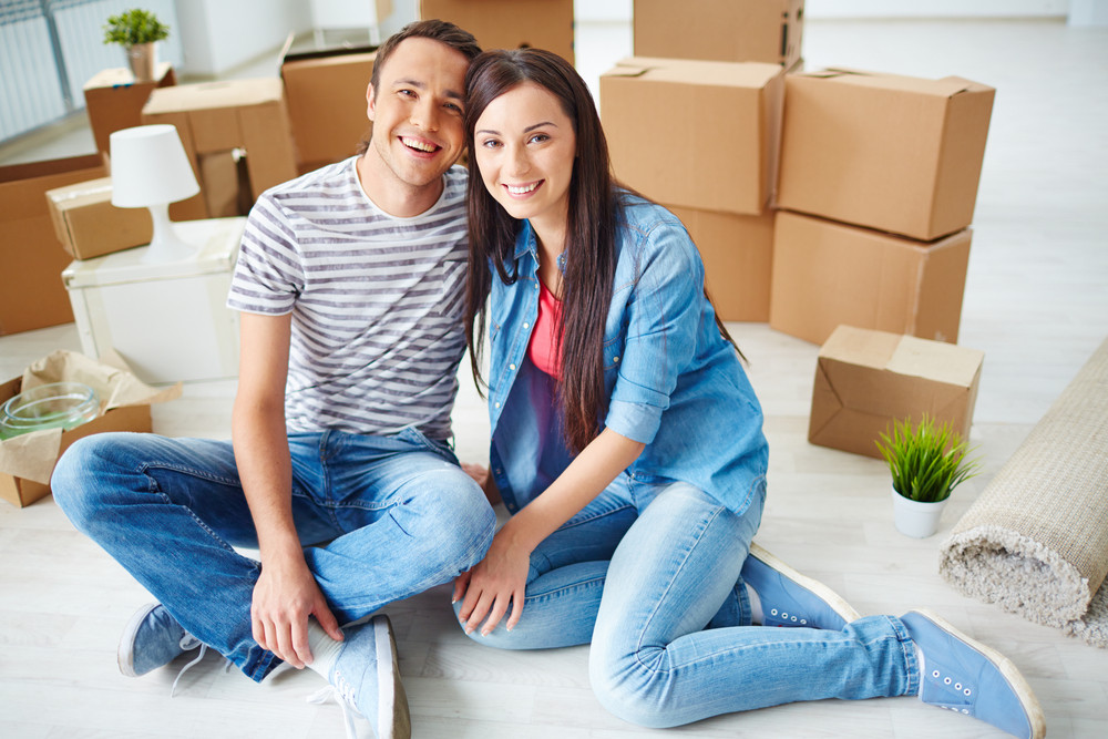 Happy Young Couple Sitting On The Floor Of New House And Looking At Camera