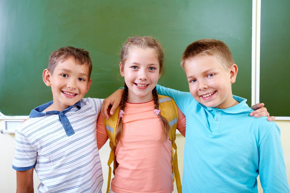 Portrait Of Lovely Girl And Two Schoolboys Looking At Camera