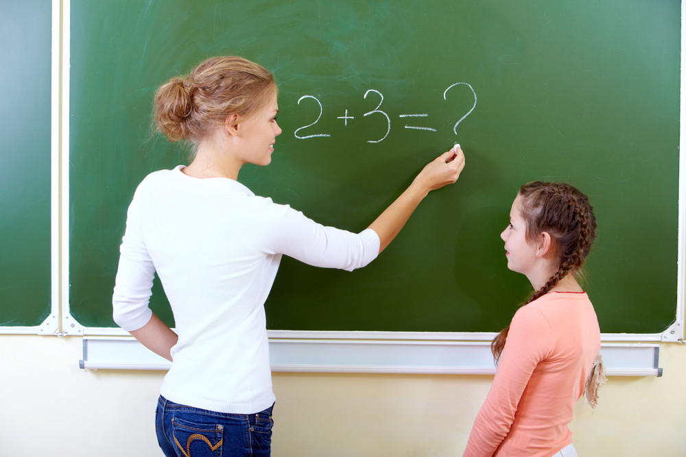 Photo Of Teacher Writing Sum On Blackboard With Pretty Pupil Near By