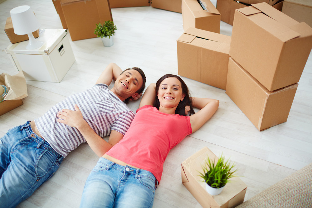 Happy Young Couple Lying On The Floor Of New House And Looking At Camera