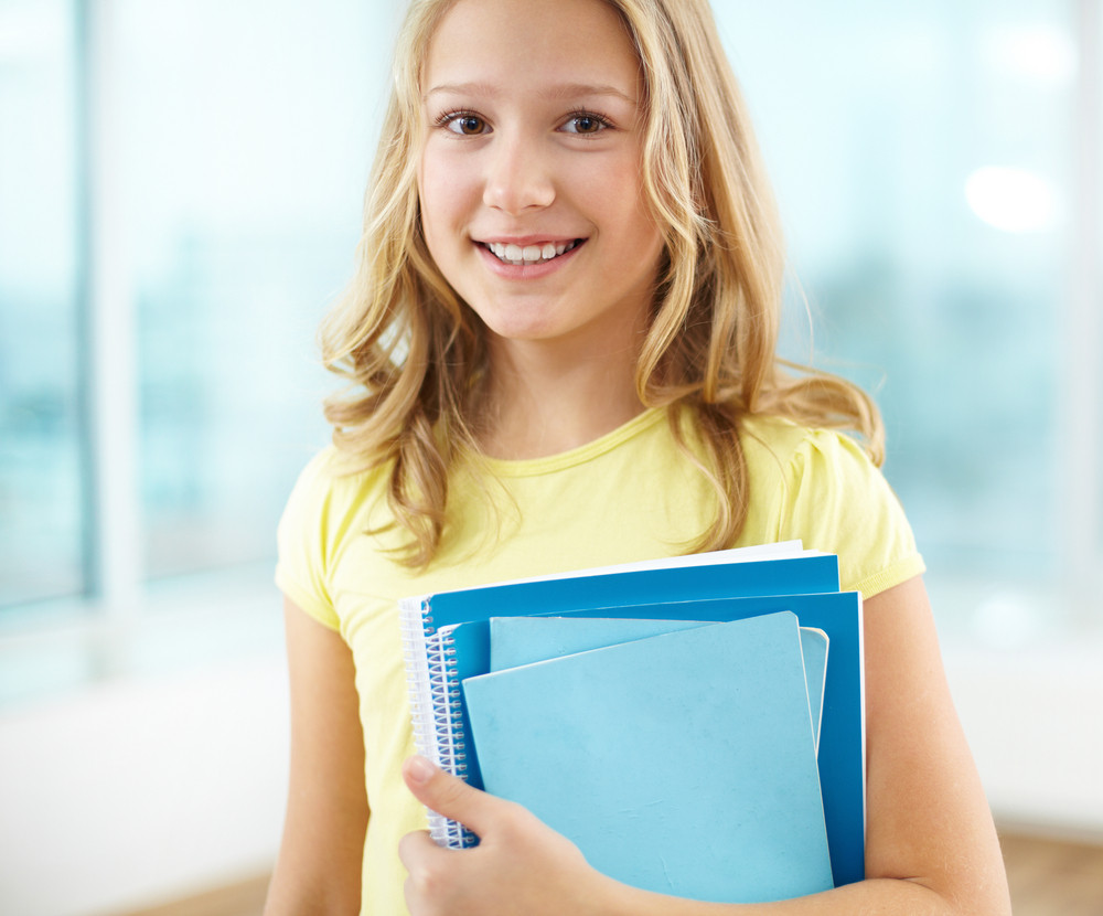 Portrait Of Cheerful Schoolgirl With Copybooks Looking At Camera