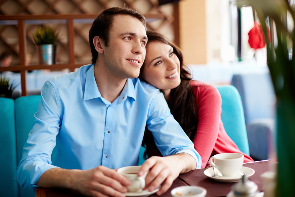 Portrait Of Amorous Young Couple Relaxing In Cafe