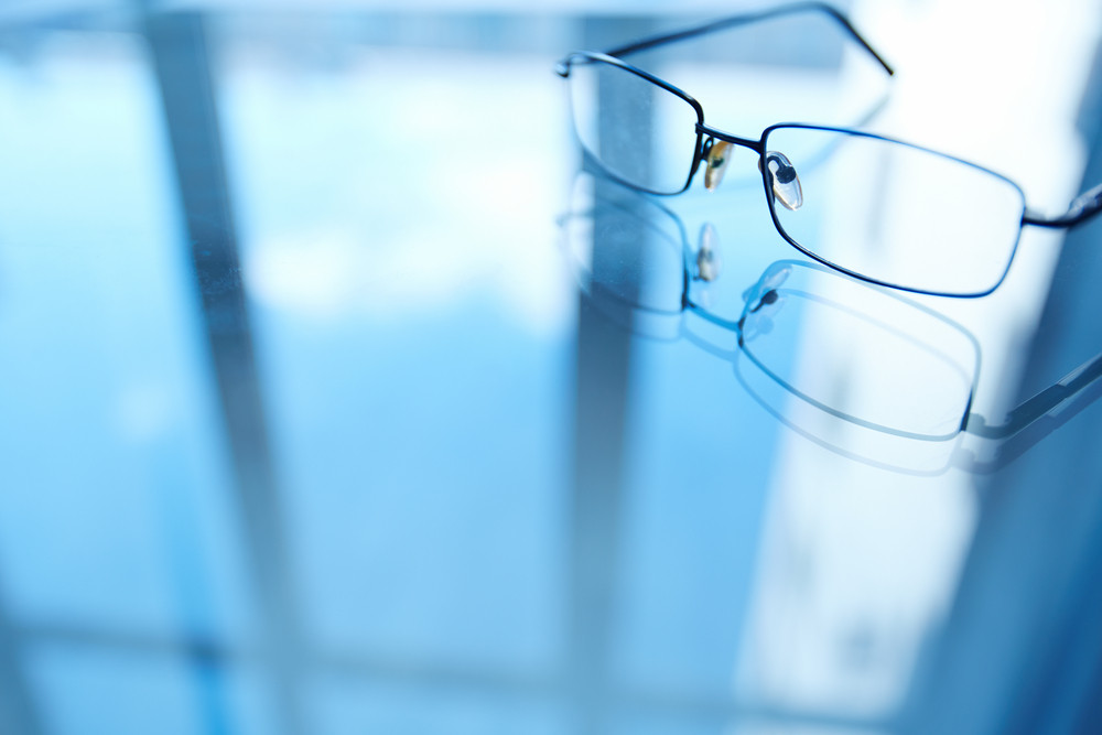 Image Of Eyeglasses On Workplace And Its Reflection