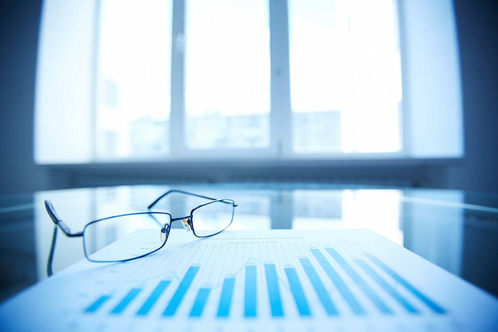 Image Of Eyeglasses And Document On Workplace