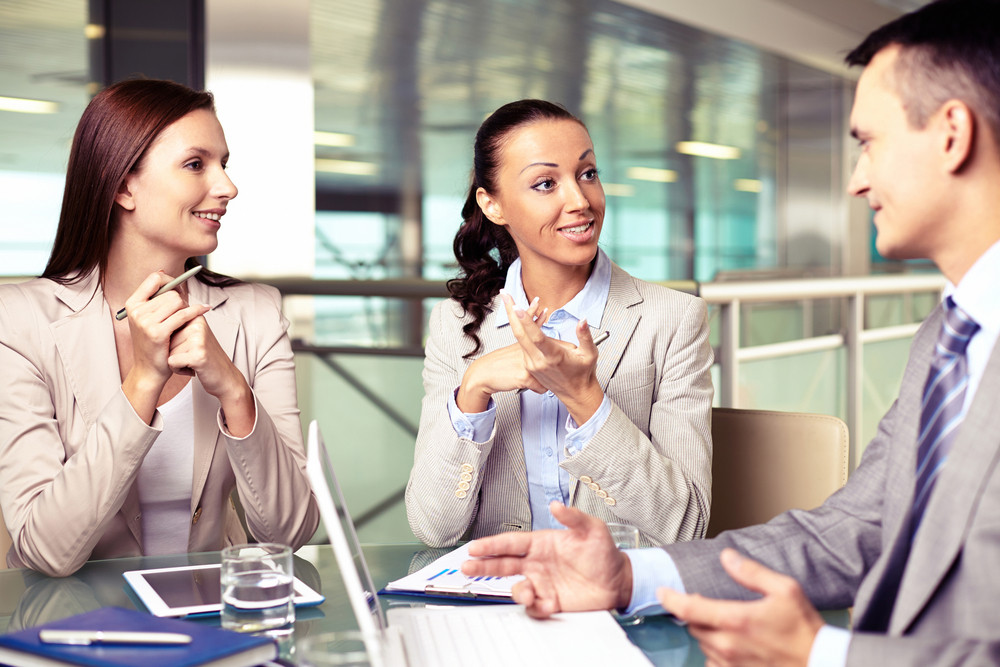 Confident Businesswomen Looking At Their Boss At Meeting While Sharing Ideas