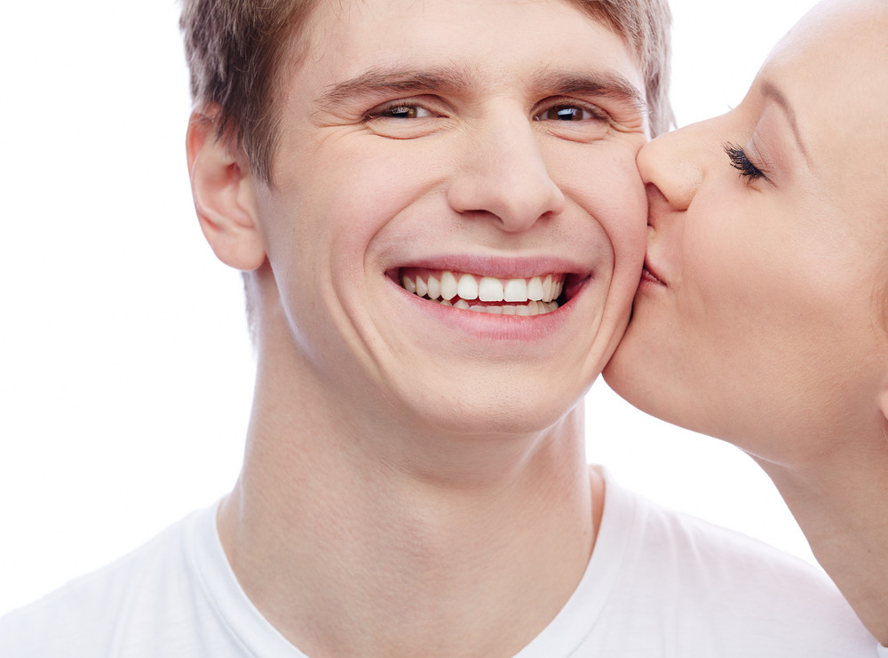 Handsome Guy Looking At Camera With Pretty Girl Near By Kissing Him In Cheek