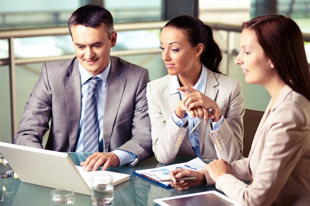 Portrait Of Confident Business Team Looking At Laptop Display At Meeting