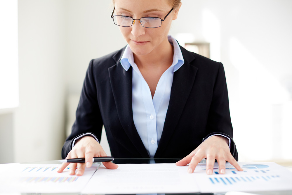 Young Businesswoman Sitting At Workplace And Working With Papers In Office