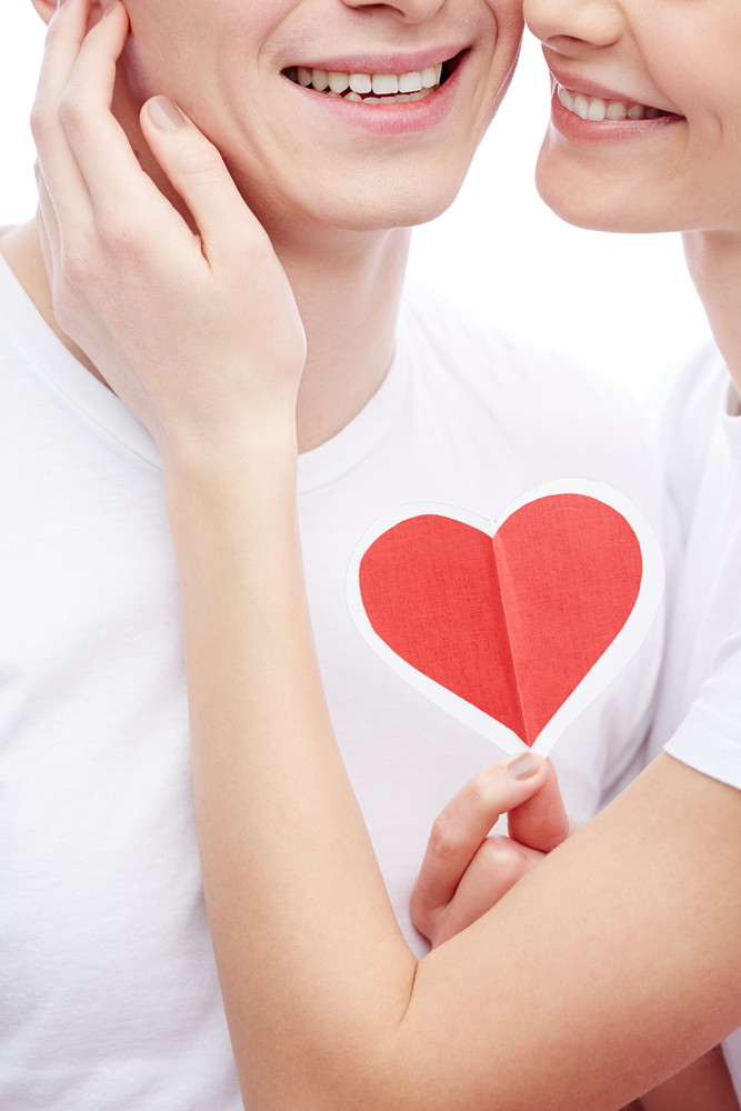 Close-up Of Amorous Young Girl Holding Red Heart And Touching Her Boyfriend Cheek