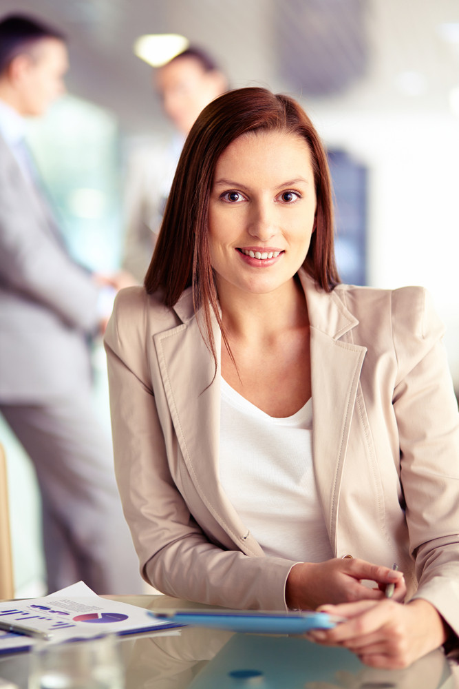 Portrait Of Friendly Specialist Looking At Camera On Background Of Working Colleagues