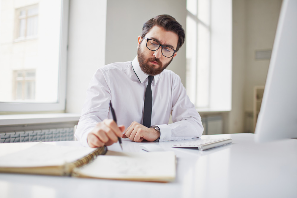 Serious Businessman Sitting In Office And Working