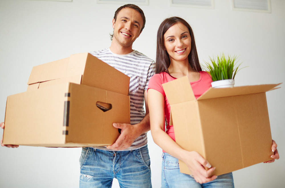 Happy Young Couple With Boxes Looking At Camera