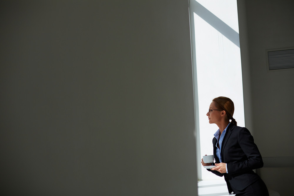 Young Businesswoman With Cup Of Tea Looking Through Window In Office