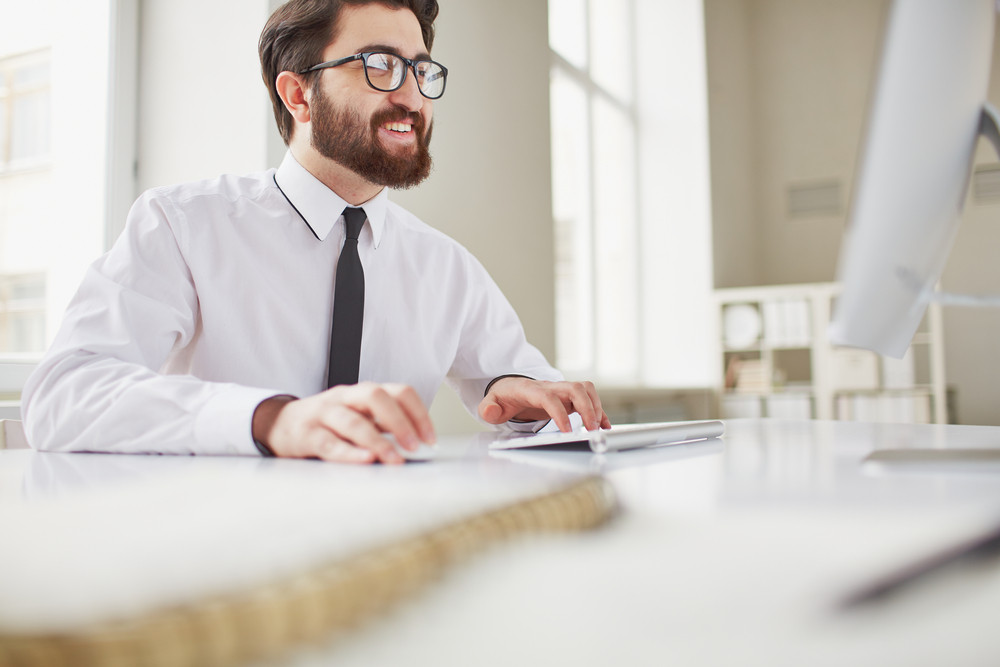 Smiling Businessman Sitting In Office And Typing