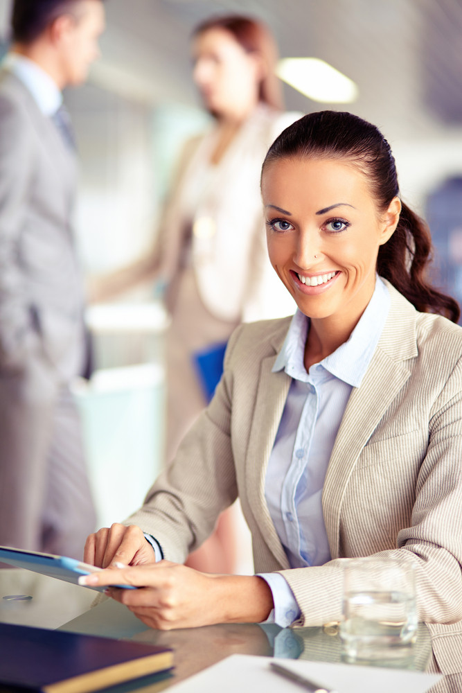 Portrait Of Confident Employee Working With Touchpad On Background Of Working Colleagues