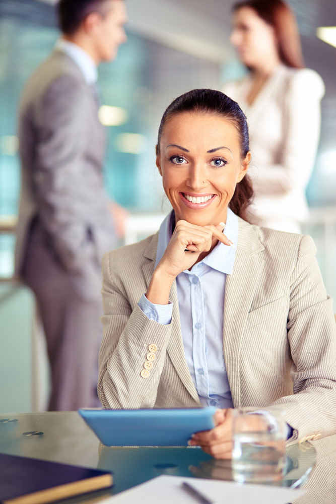 Portrait Of Confident Employee With Touchpad Looking At Camera On Background Of Working Colleagues