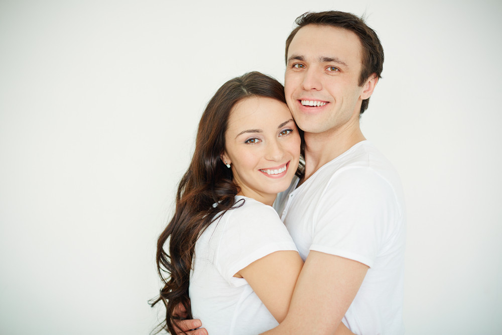 Portrait Of Amorous Young Woman And Man Embracing And Looking At Camera