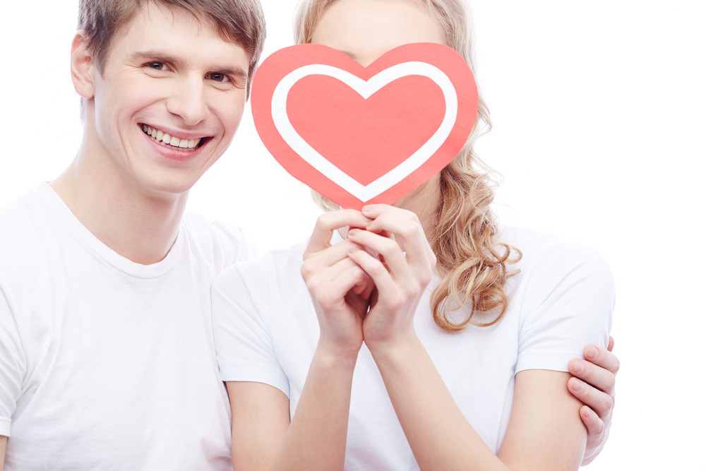 Portrait Of Happy Guy Looking At Camera While Embracing His Girlfriend With Red Heart By Her Face