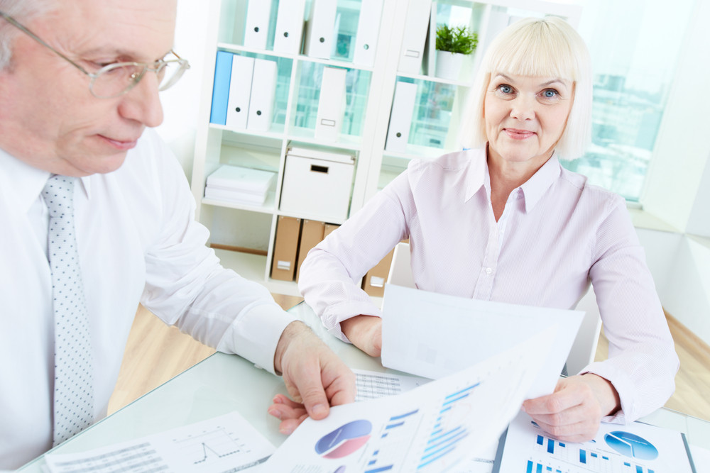 Portrait Of Mature Businesswoman Looking At Camera With Smile While Paperworking With Her Partner At Meeting