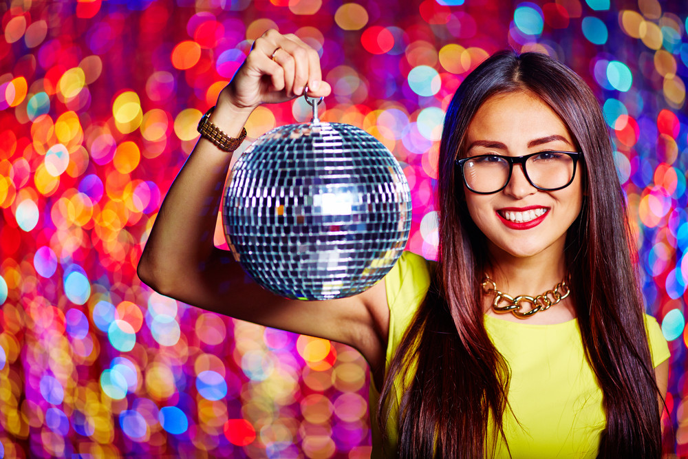 Portrait Of Glamorous Asian Girl With Sparkling Disco Ball Looking At Camera