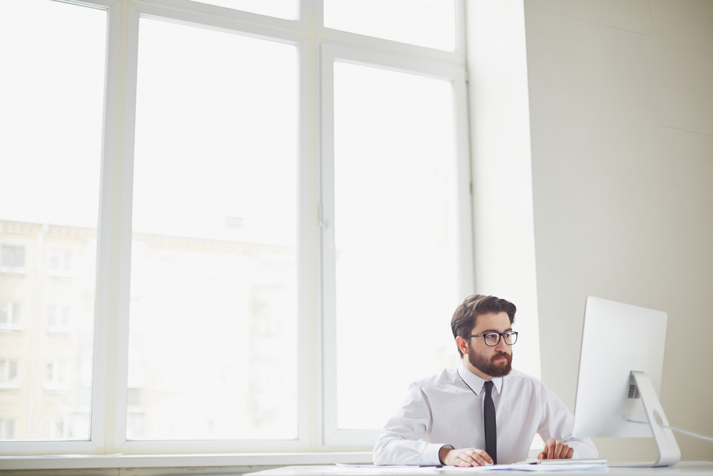 Serious Businessman Sitting In Office And Networking