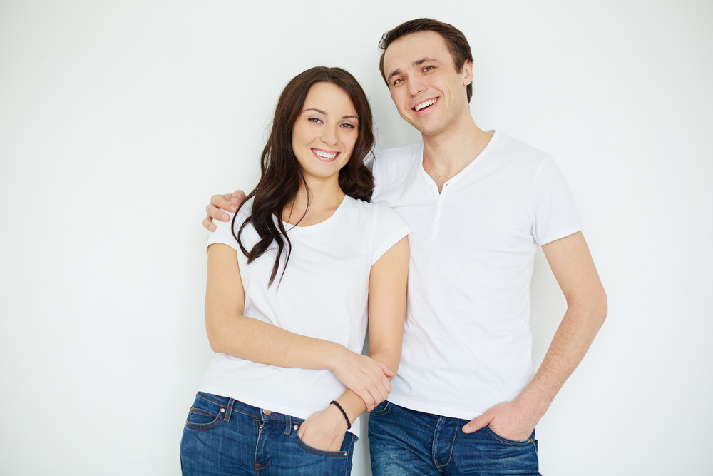 Portrait Of Amorous Young Couple Looking At Camera In Isolation