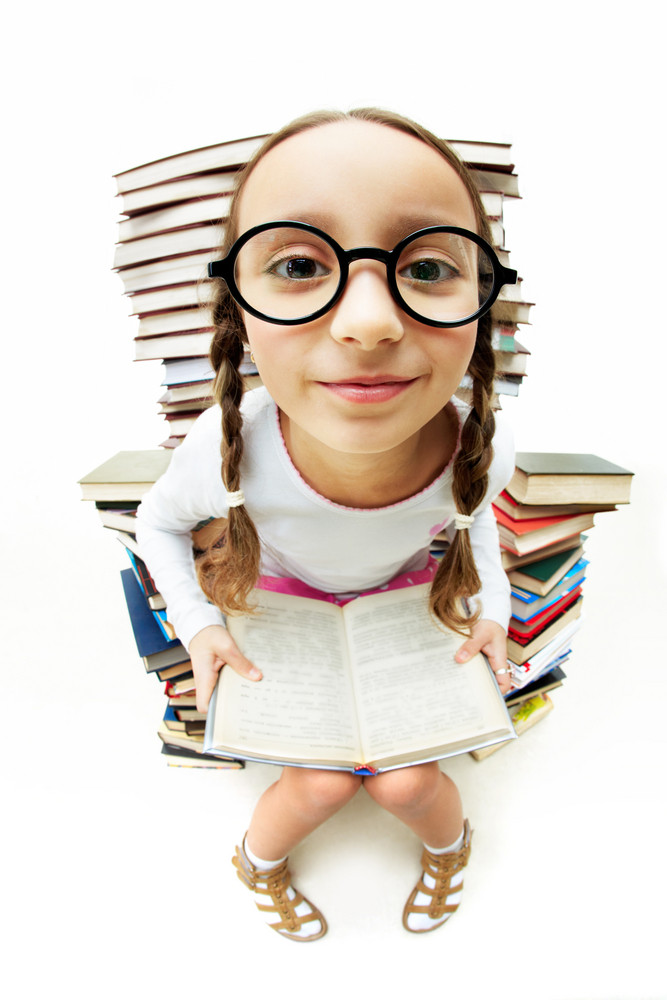 Portrait Of Diligent Pupil Sitting On Pile Of Books And Looking At Camera