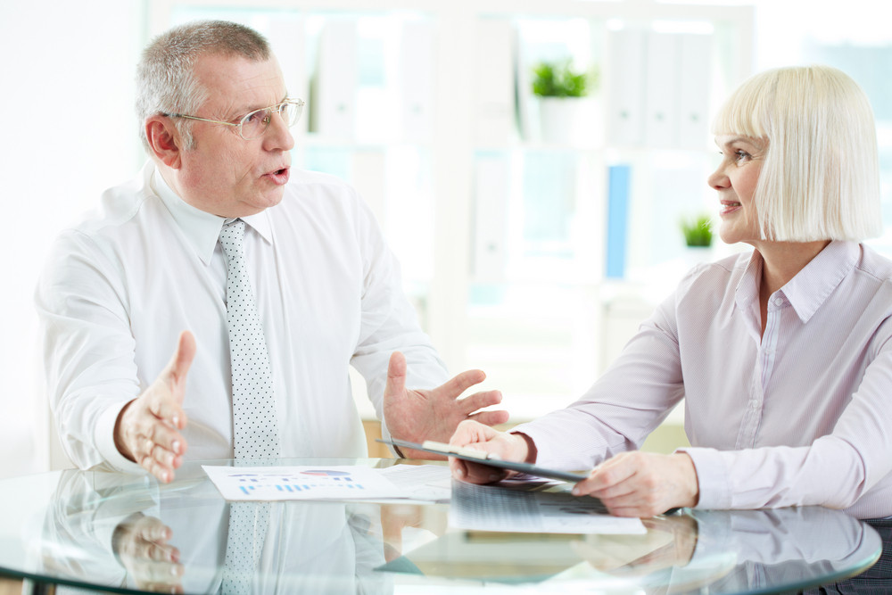 Portrait Of Mature Businesswoman Listening Attentively To Her Boss Explanations At Meeting