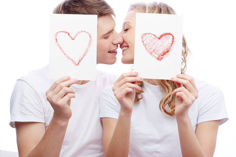 Portrait Of Young Amorous Couple Kissing While Holding Papers With Hearts