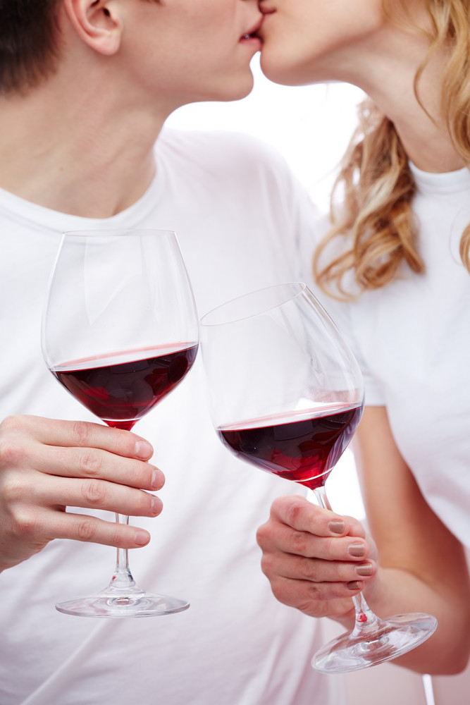 A Young Happy Couple Holding Glasses With Red Wine And Kissing