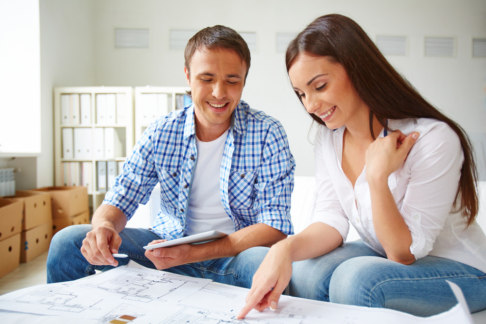 Portrait Of Young Couple During Discussion Of Plan Of Flat