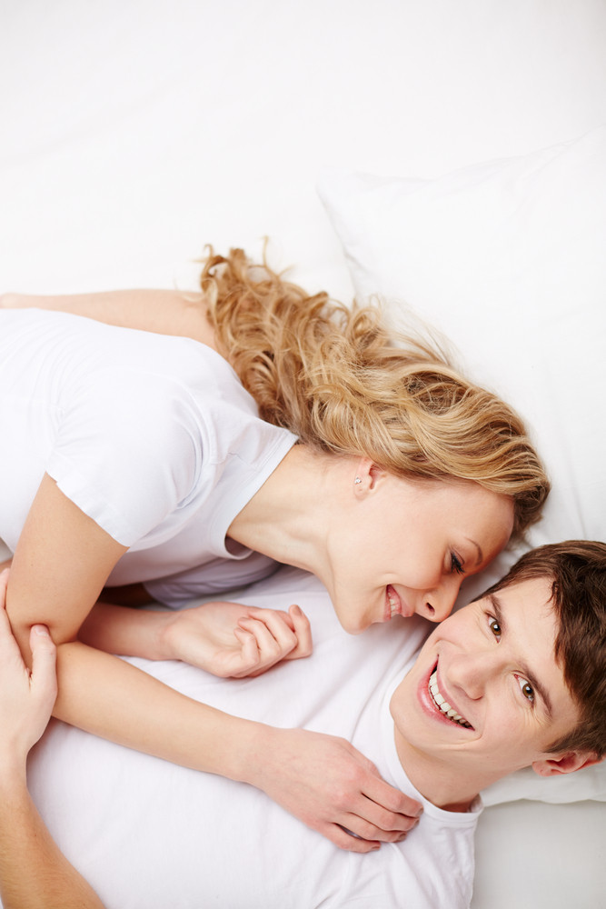 Portrait Of Happy Guy Looking At Camera With His Girlfriend Lying Near By