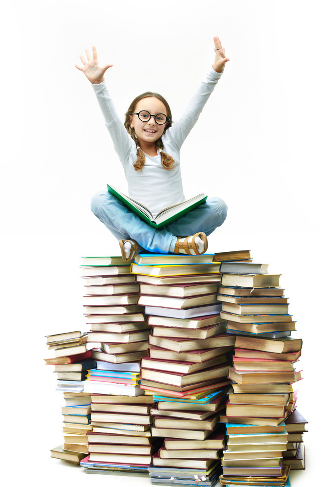 Portrait Of Cute Girl Sitting On Pile Of Books With Raised Arms