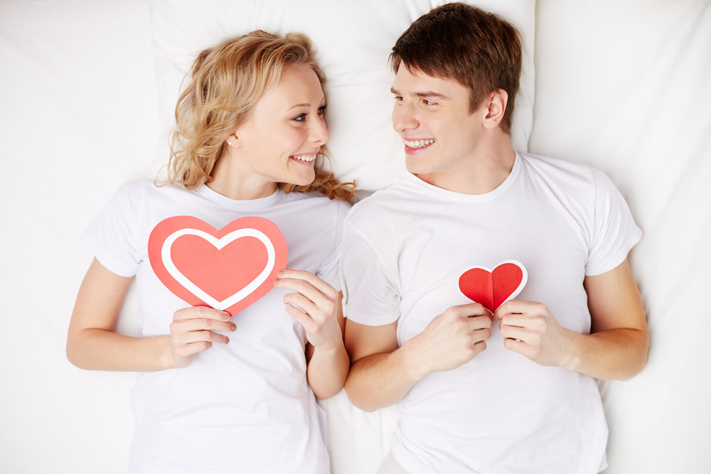 Portrait Of Happy Guy And His Girlfriend Holding Red Hearts By Their Chest And Looking At One Another