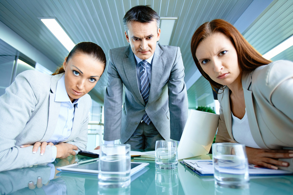 Serious Boss With His Two Employees Looking At Camera With Displeasure