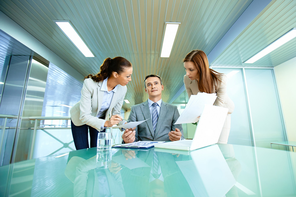 Inspirated Boss Sitting At Workplace Surrounded By Two Secretaries