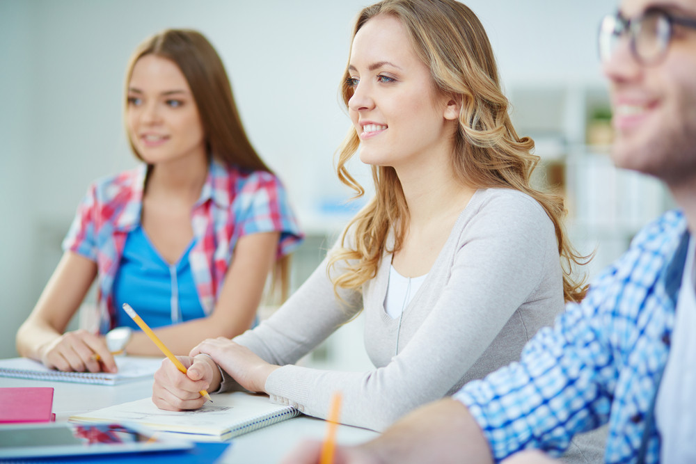 Smart Girl Listening To Teacher At Seminar With Her Groupmates Near By