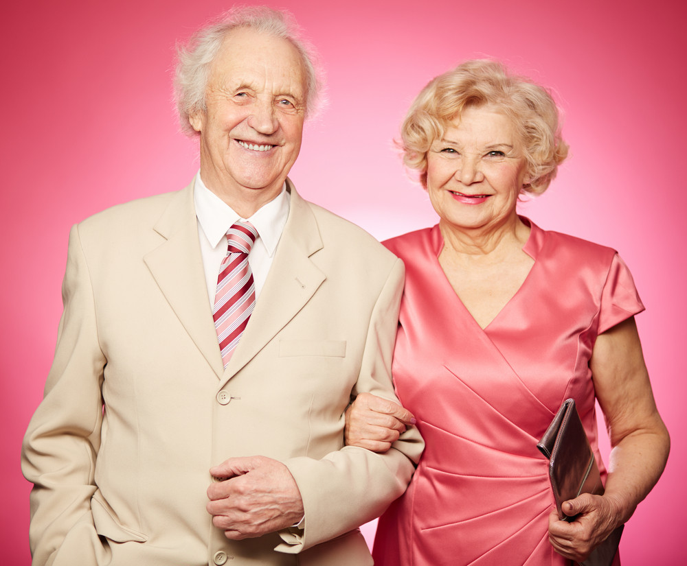 Portrait Of A Charming Retired Couple Posing Against Pink Background