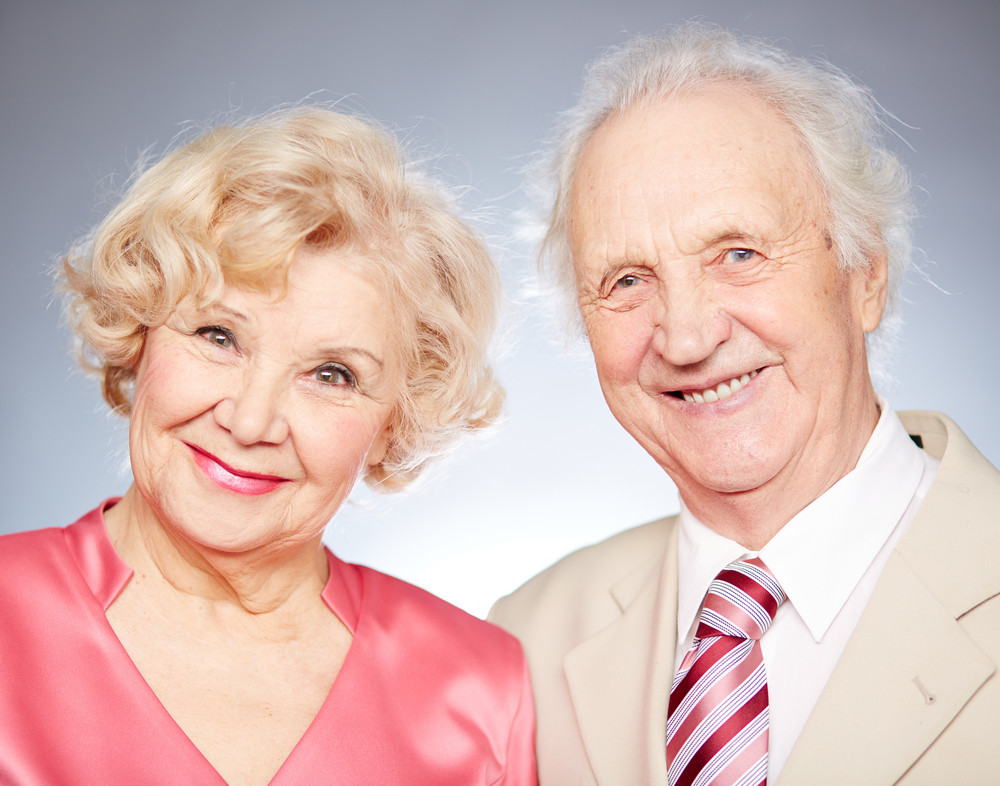 Portrait Of A Charming Retired Couple Looking At Camera In Isolation