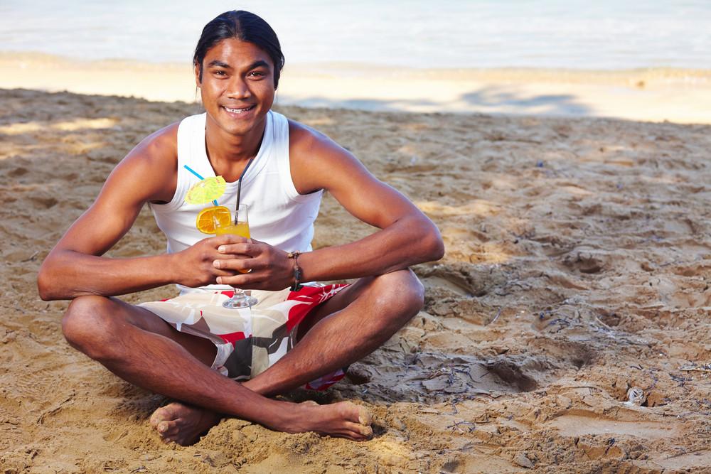Happy Latino Man Having Fresh Drink By The Seaside