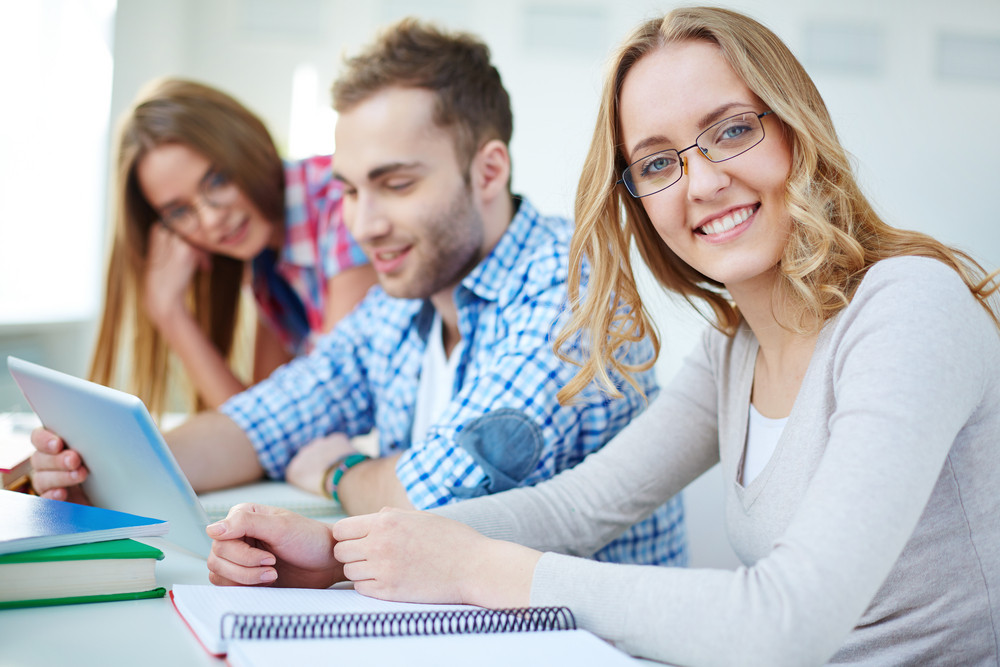 Portrait Of Cute Teenager Looking At Camera On Background Of Her Friends Using Touchpad